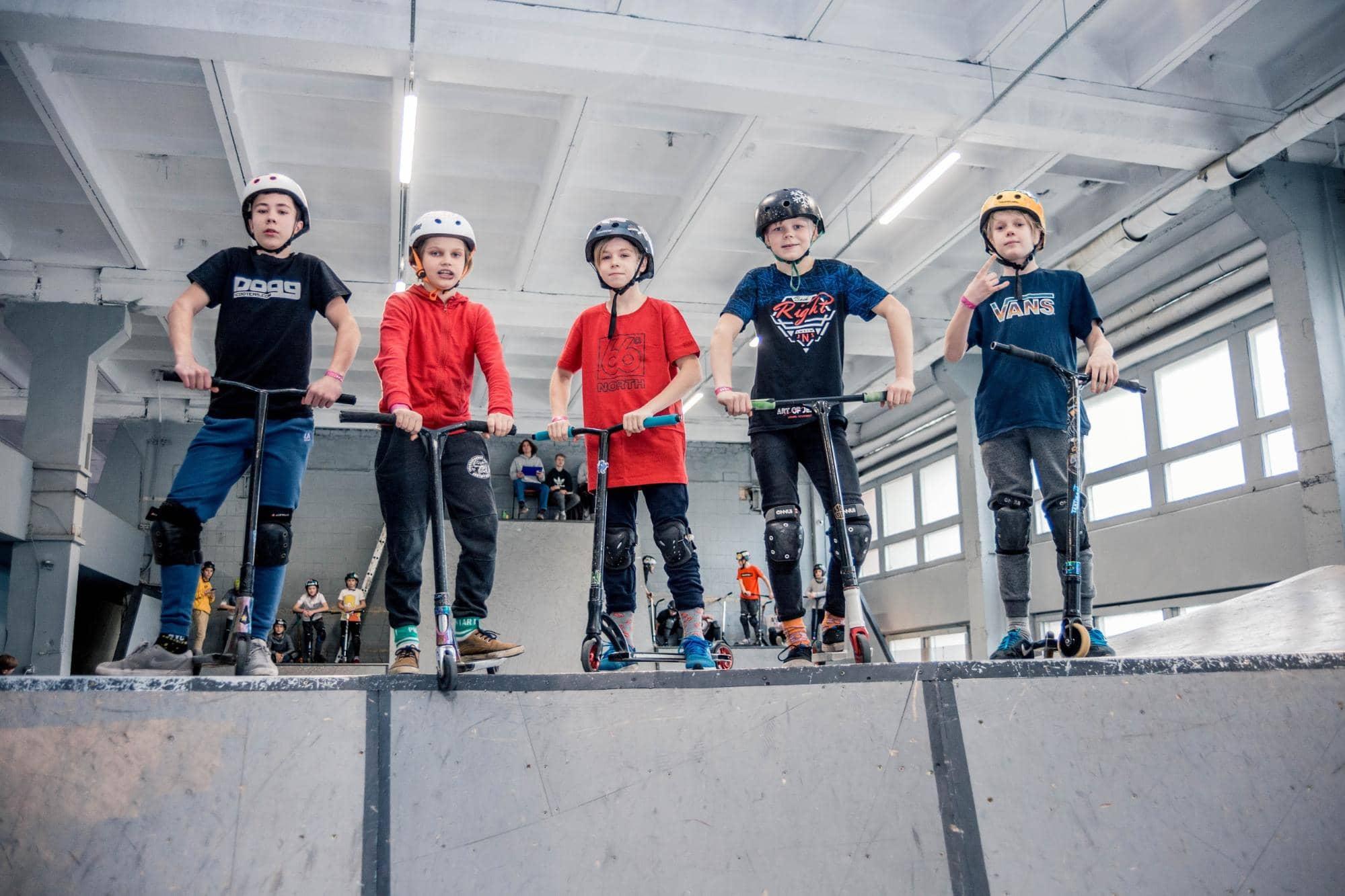 Коллективное фото детей с трюковыми самокатами в скейтпарке